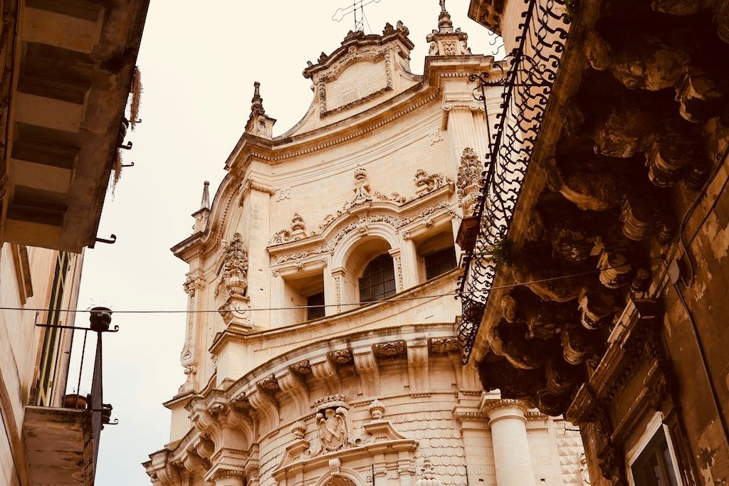 Blick durch eine enge Gasse hinauf zu einer Kirchenfassade. Die Kirche ist aus hellem Kalkstein gebaut und über und über mit Ornamenten überzogen.