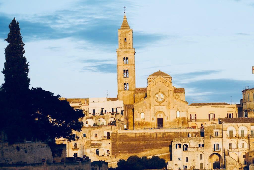 Das Bild zeigt den Kirchturm der Kathedrale von Matera. Neben dem Kirchturm erhebt sich eine dreischiffige Kirche mit einer niedrigen Kuppel. Links im Bild wächst eine Zypresse. Der Himmel ist blau aber das Licht zeigt, dass dieses Bild am Abend aufgenommen worden ist.