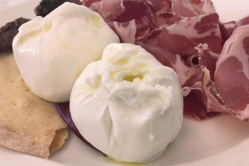 Zwei kleine, weiße Käsekugel mit etwas Schinken auf einem Teller serviert.