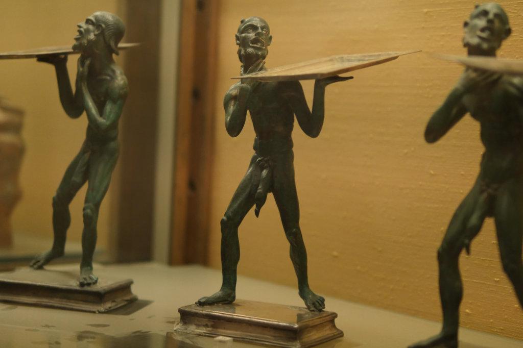 3 Bronzefigürchen mit großen Köpfen und maskenhaften Gesichtern tragen kleine silberne Tabletts. Sie stehen in einer Vitrine des Nationalmuseum Neapel