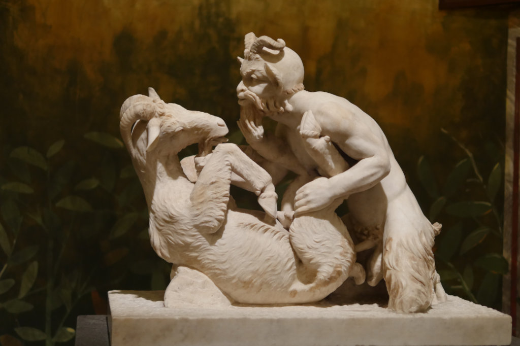 Marmorskulptur eines Ziegenbock auf dem Rücken, der von einem Faun anal penetriert wird, in einer bemalten Nische im geheimen Kabinett des Nationalmuseum Neapel..