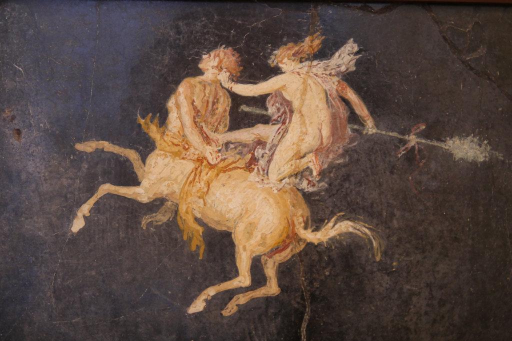 Diese Wandmalerei aus Pompeji zeigt einen Kentauern, ein Pferd mit Männeroberkörper, auf dem eine junge Frau reitet.