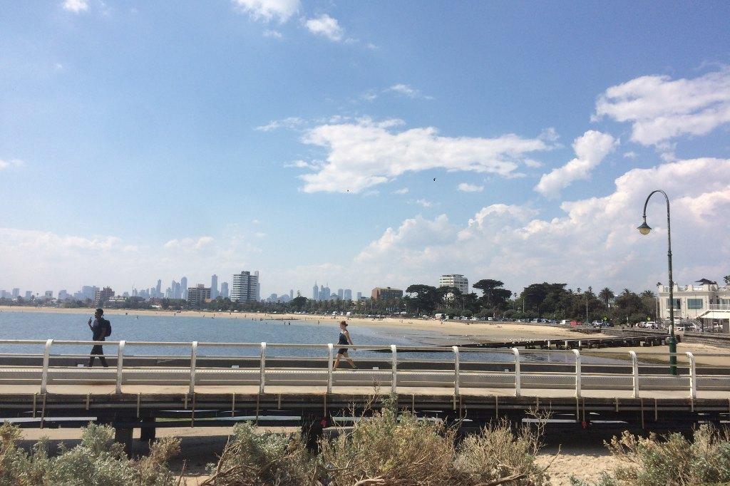 Ein Steg läuft quer durchs Bild. Auf ihm gehen Menschen. Im Vordergrund deutet sich der Stadtstrand von St. Kilda an, im Hintergrund die Skyline von Melbourne.