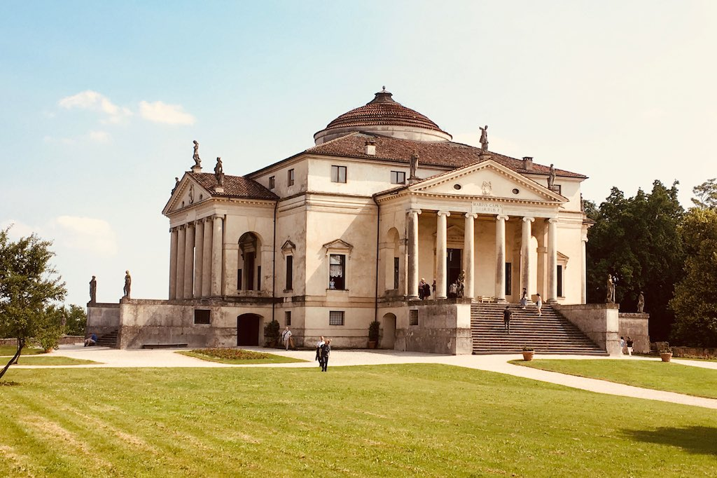 Ein Garten vor den Stadttoren von Vicenza. Auf einer grünen Wiese steht ein würfelartiges Haus mit Säulenportikus und Tempelgiebel. Die Villa Rotonda von Palladio