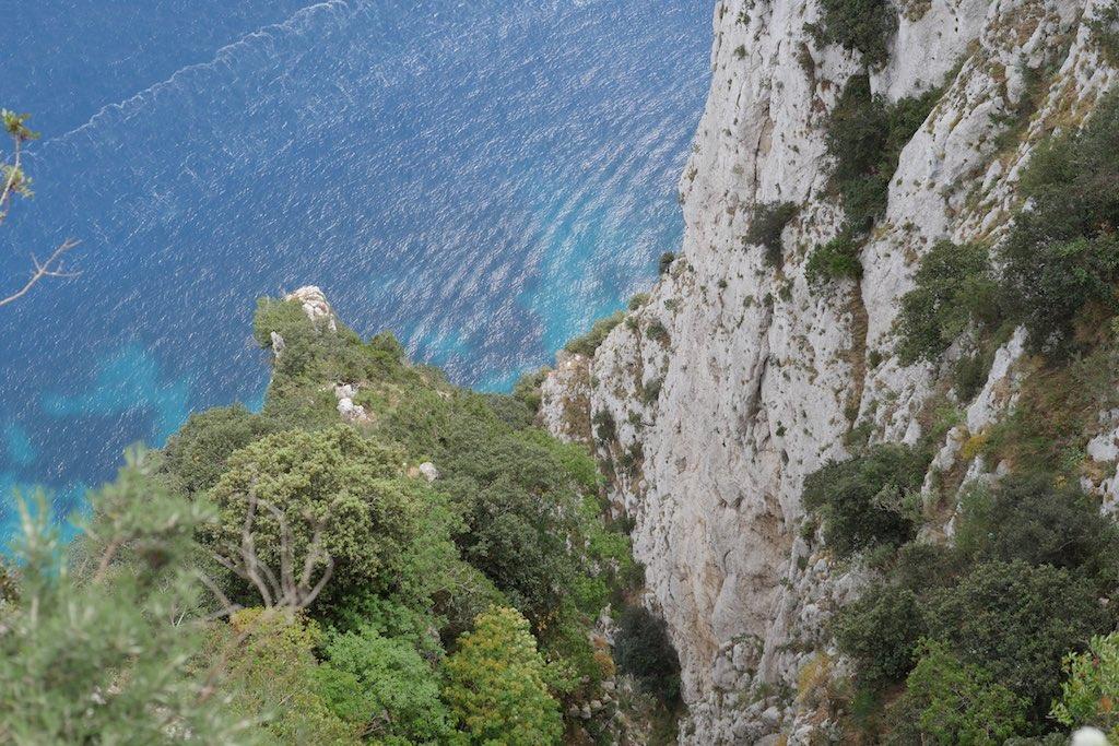 Blick die Steilküste von Capri hinunter auf das blaue Meer.