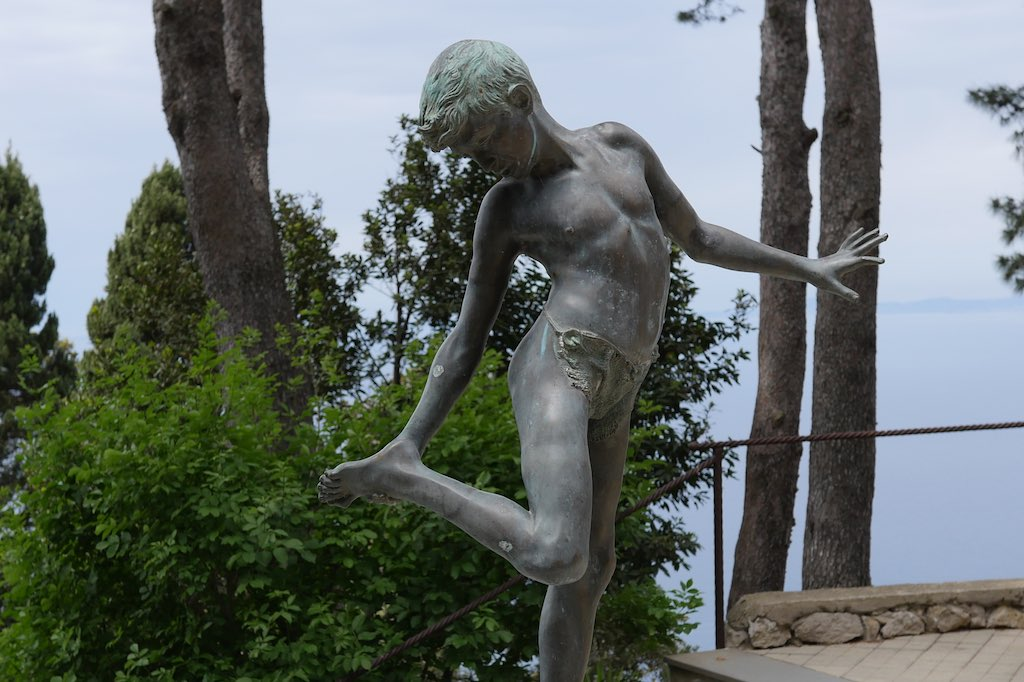 Skulptur eines tanzenden Knaben im Garten der Villa Lysis.