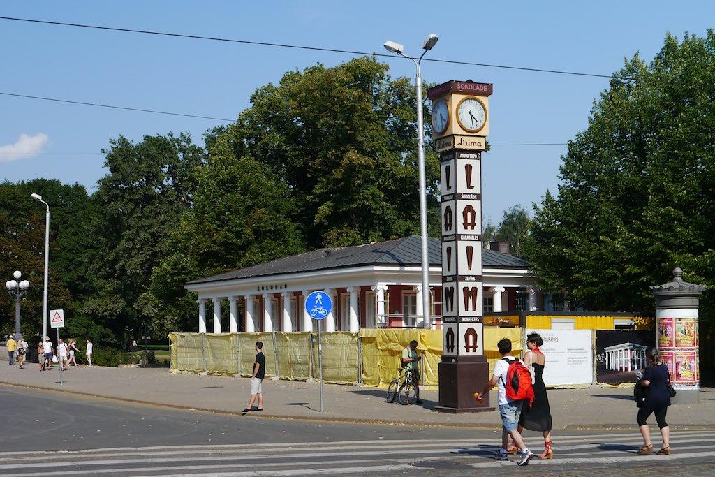 Das Bild zeigt eine Straßenkreuzung in Riga. Auf der rechten Seite stehen Bäume eines Parks. Am Straßenrand ein weißes Gebäude mit Säulen. Davor eine Uhr mit dem Schriftzug Laima.