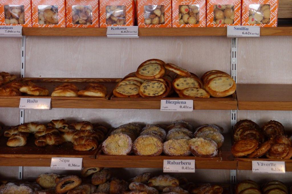 Regal in einer Bäckerei mit Backwaren. Im obersten Regal sind Schachteln mit Keksen zu sehen, dadrunter verschiedene frische Backwaren aus Blätter- oder aus Hefeteig.