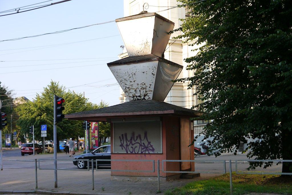 Das Bild zeigt eine Straßenkreuzung in Riga. im Zentrum der Kreuzung steht ein kleiner Pavillon auf quadratischem Grundriss. Besonders ist das Dach, das mit zwei auf den Kopf gestellten Pyramiden dekoriert ist.