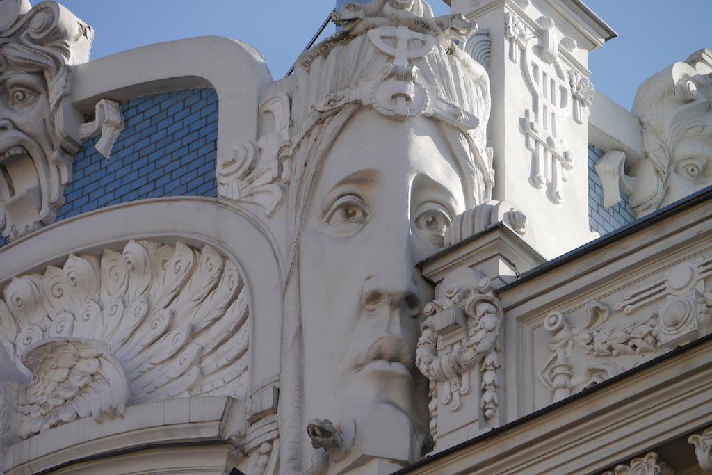 Das Bild zeigt den Giebel eines Hauses in Riga. Der Giebel ist mit blauen Ziegeln und weißen Ornamenten verziert. Im Zentrum des Bildes eine große Maske, die ein trauriges Frauengesicht darstellt. Links ist das Ornament eines Pfauenrads zu sehen. Ein absoluter Riga Tipp ist der Besuch der Alberta Straße mit ihren Jugendstilhäusern.