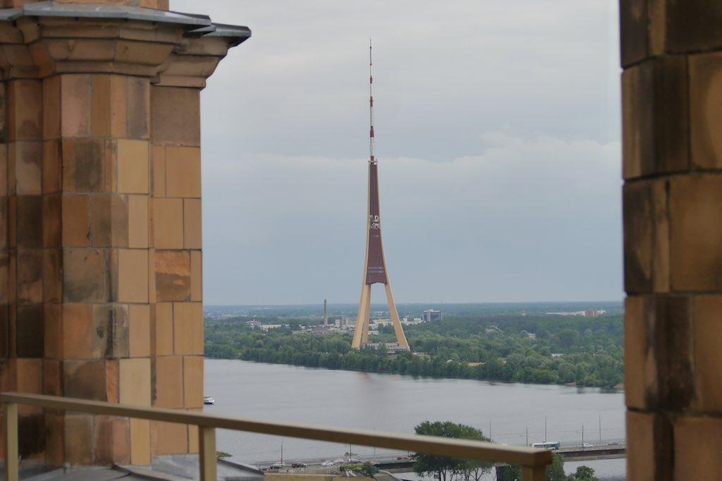 Das Bild zeigt den Ausblick vom Haus der Wissenschaft auf den Fluss Düna und die Insel, auf der der Fernsehturm von Riga steht. Der Fernsehturm sieht aus wie ein eleganter Grashalm.