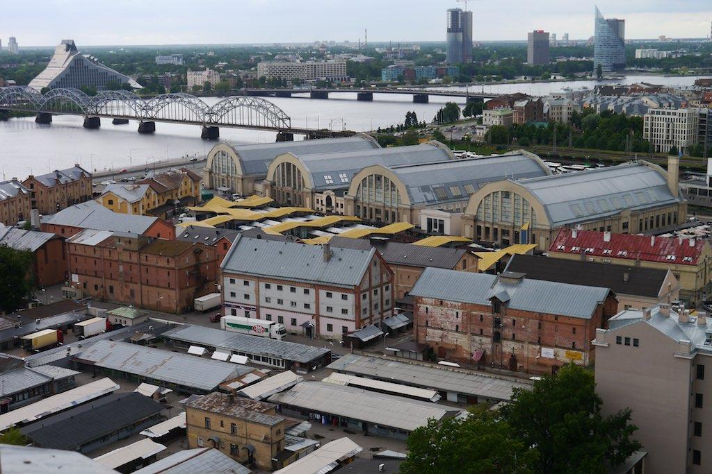 Das Bild zeigt den Blick aus der Vogelperspektive auf die großen Hallen des Zentralmarkts von Riga. Die Hallen haben große Fenster und runde Dächer mit die grauem Metal gedeckt sind. Ein Besuch auf dem Zentralmarkt ist ein absoluter Riga Tipp. Auf keinen Fall verpassen.
