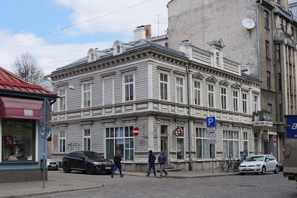 An einer Straßenecke steht ein zweistöckiges Holzhaus. Die Wände sind grau. Die Fensterrahmen und die Ornamente am Haus sind weiß. Das Holzhaus wird von einem mehrstöckigen Haus aus Backstein überragt.