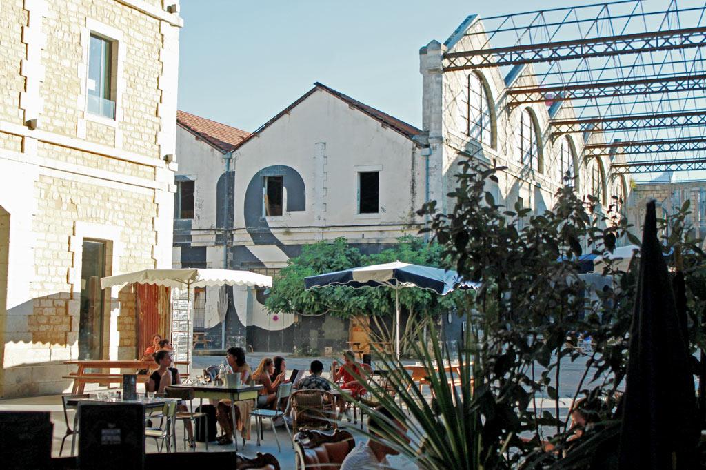 """Leute trinken Kaffee im Industrie-Ambiente des Bistro """"Magasin Général"""" – Bordeaux im Sommer: Am Fluss spielt die Musik"""