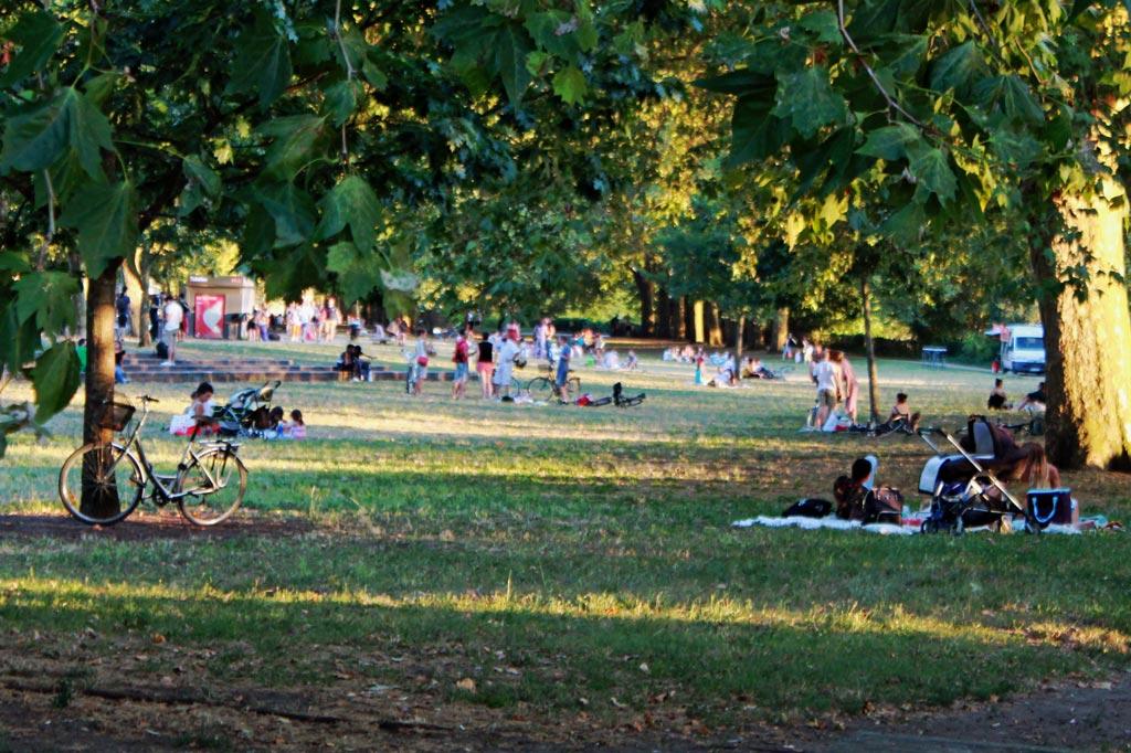 Laues Ende eines heißen Tages: Picknick im Parc aux Angéliques am Ufer der Garonne ALT: Verstreute Menschengruppen unter Bäumen auf einer Wiese des Parc aux Angéliques am Ufer der Garonne – Bordeaux im Sommer: Am Fluss spielt die Musik