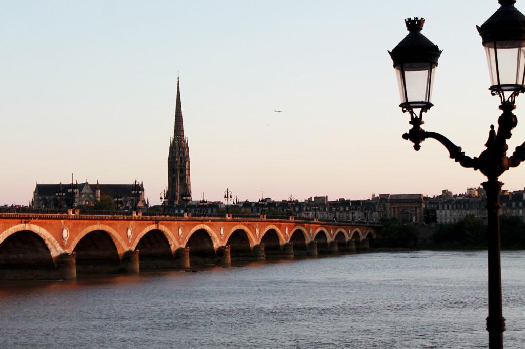 Brückenpfeiler für Brückenpfeiler schreitet der geziegelte Pont Saint-Jean im Abendlicht über die Garonne zur Altstadt von Bordeaux – Bordeaux im Sommer: Am Fluss spielt die Musik