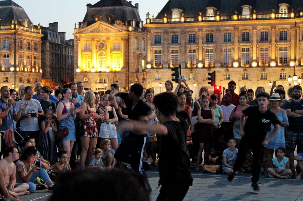 Breakdance-Performance vor der angestrahlten Altstadtkulisse von Bordeaux – Bordeaux im Sommer: Am Fluss spielt die Musik