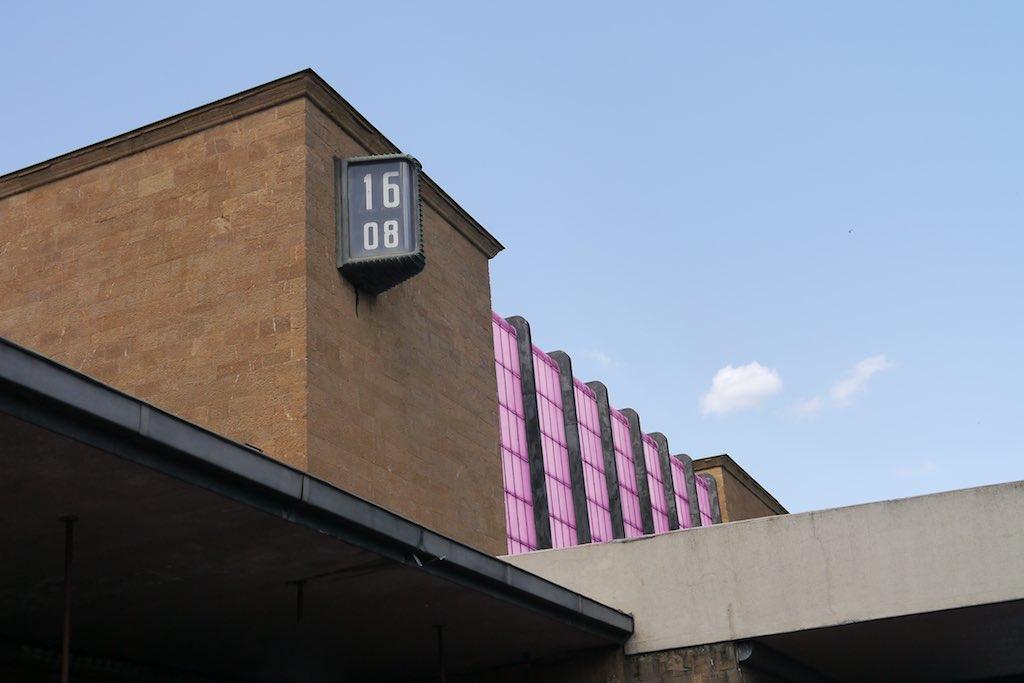 Das Bild zeigt ein Detail des modernen Bahnhofsgebäudes von Florenz. Ein Kubus aus gelbem Stein schiebt sich diagonal ins Bild. An diesem Kubus ist eine Uhr angebracht. Sie zeigt die Uhrzeit 16 Uhr 8.