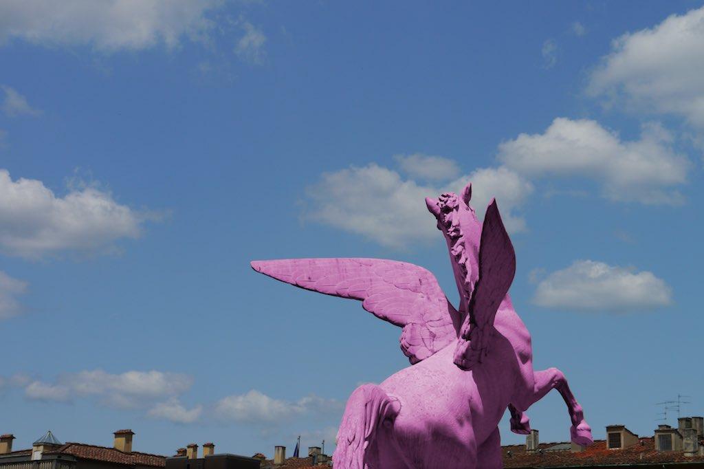 Das Bild zeigt den blauen Himmel über Florenz. Am Horizont sind einige Schornsteine zu sehen. Im Vordergrund steht ein Pferd mit Flügeln. Es sieht so aus, also ob das Pferd fliegen könnte.
