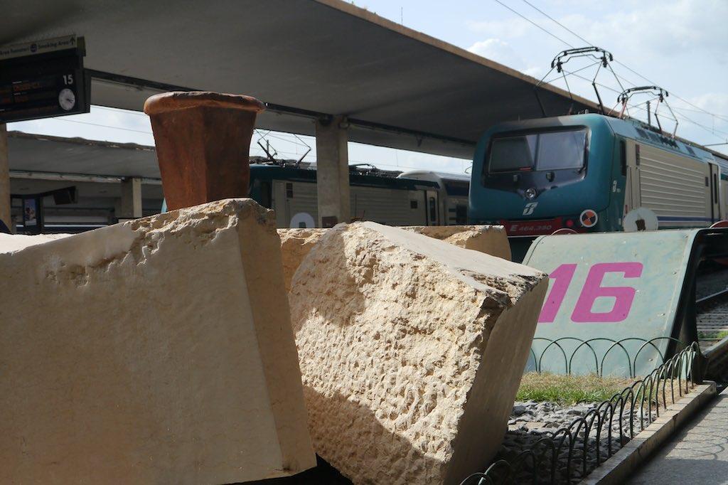Das Bild zeigt ein Gleis im Bahnhof Santa Maria Novella von Florenz. Eine Lokomotive ist diagonal im Bild zu sehen, neben der Lokomotive die Überdachung des Bahnsteigs. Vor der Lokomotive befindet sich ein Stoper auf den die Zahl 16 geschrieben ist. Vor dem Stoper sind Grobe Steinblöcke aufgeschichtet.