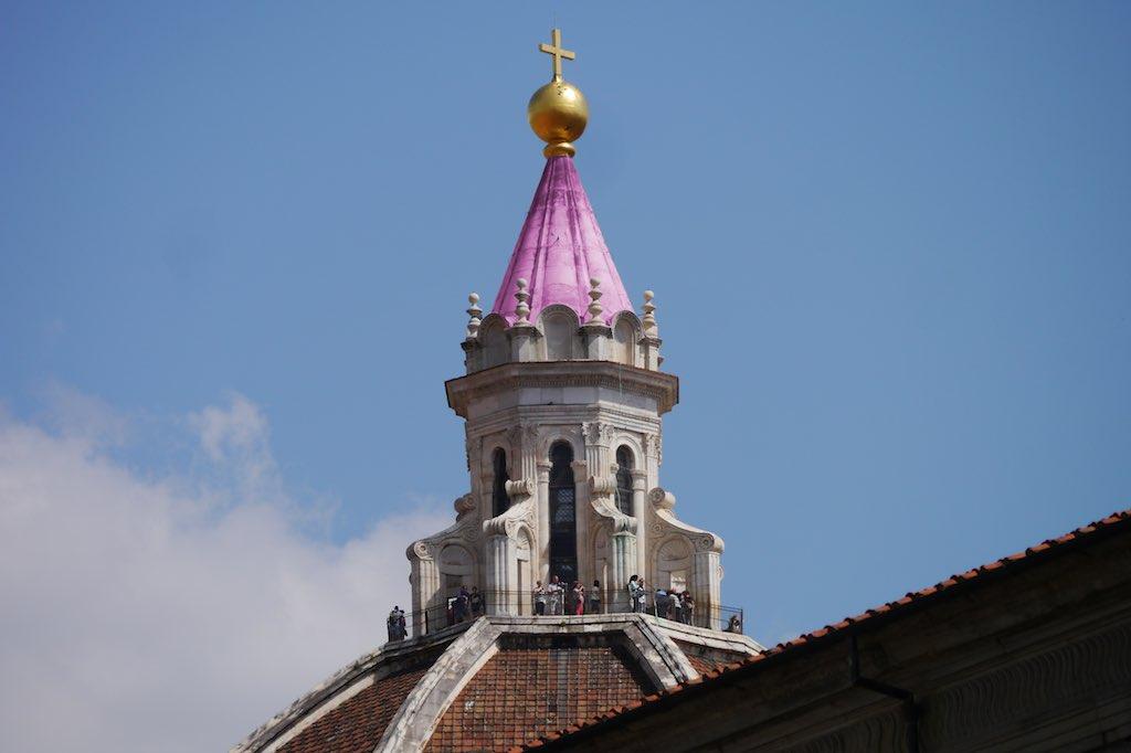 Das Bild zeigt die Laterne der Domkuppel von Florenz. Die Laterne sieht aus wie ein achteckiger Vogelkäfig. Auf den achteckigen Bau ist ein Kegel gesetzt, der von einer goldenen Kugel bekrönt wird. Auf der Kugel steht ein goldenes Kreuz.