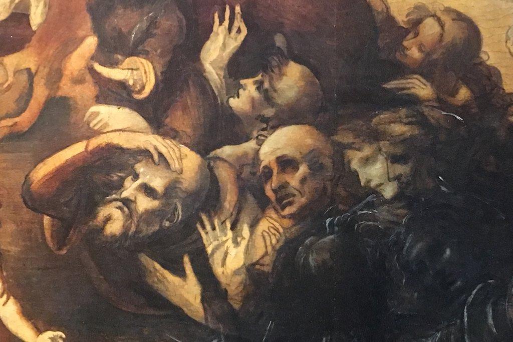 Dieses Meisterwerk aus den Uffizien zeigt den Ausschnitt aus einem Gemälde Leonardo da Vincis. Zu sehen sind Skizzen von Köpfen und Körpern. Die dargestellten Männer haben die Hände erhoben oder schlagen sie sich an die Stirn.