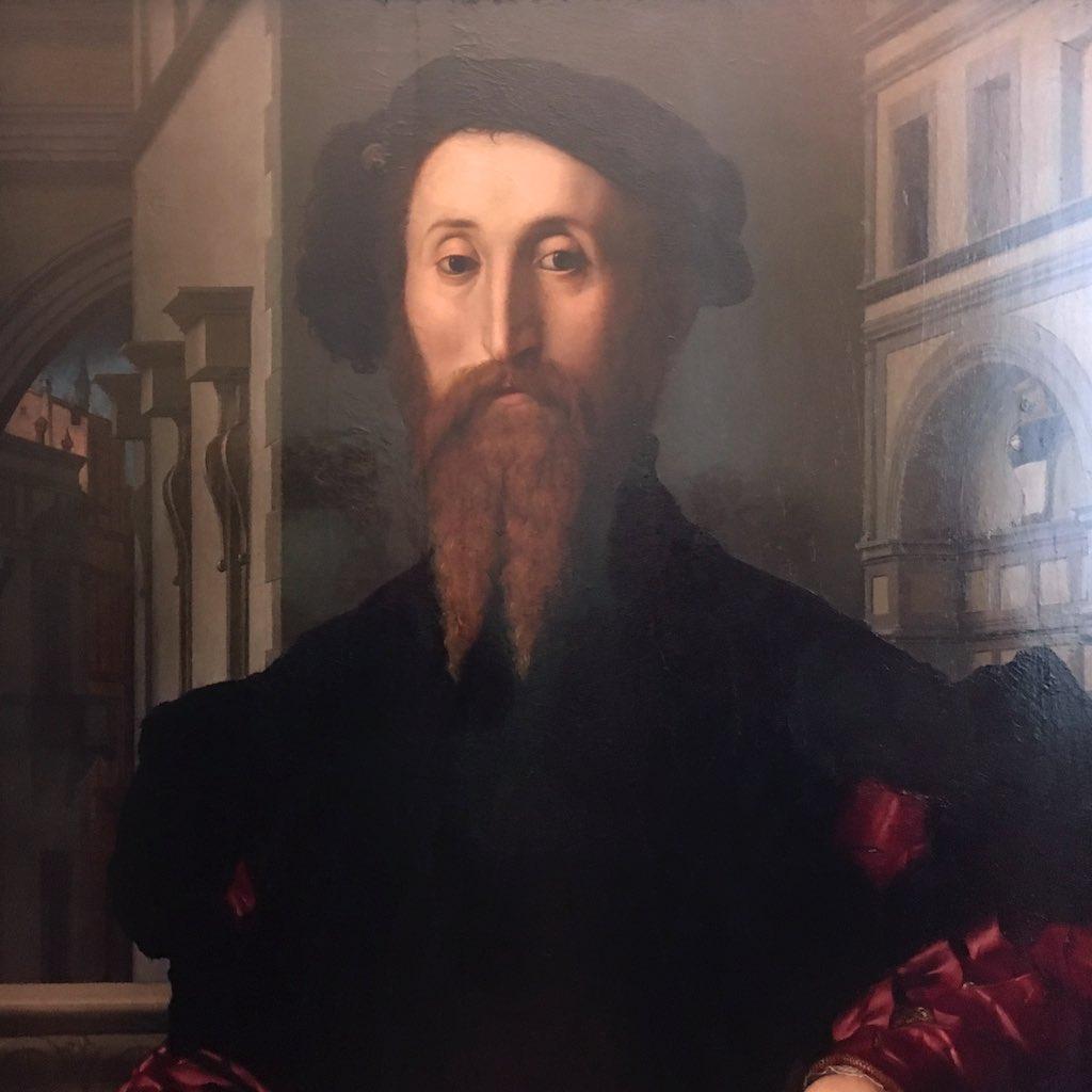 Mann mit einen schwarzen Barett auf dem Kopf in dem Innenhof der Uffizien.