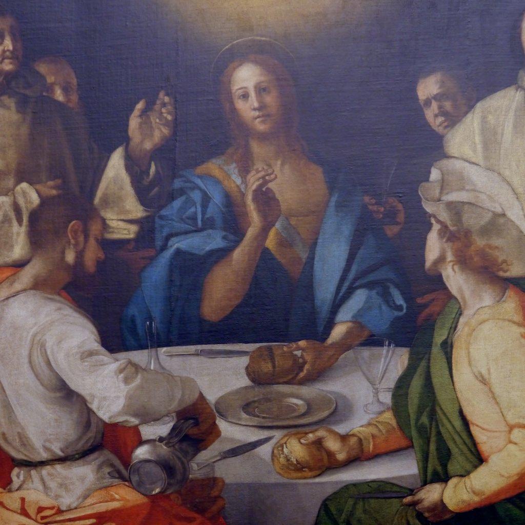 Drei Männer sitzen um einen Tisch, auf dem Gläser, Teller und Brot gestellt sind. Im Hintergrund sieht man Mönche, die die Szene beobachten.