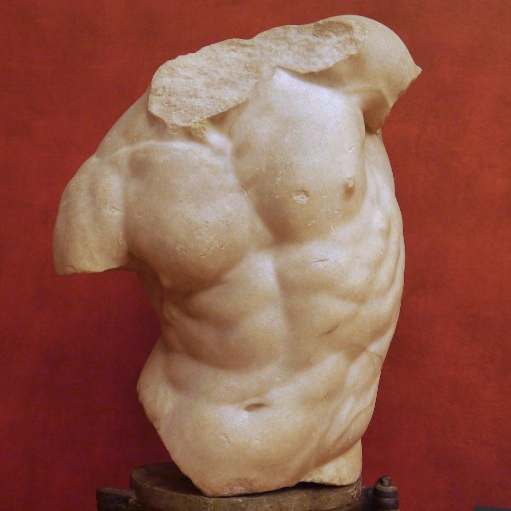 Ein muskulöser Oberkörper aus weißem Marmor vor einer roten Wand. Römisches Meisterwerk nach einem griechischen Original.