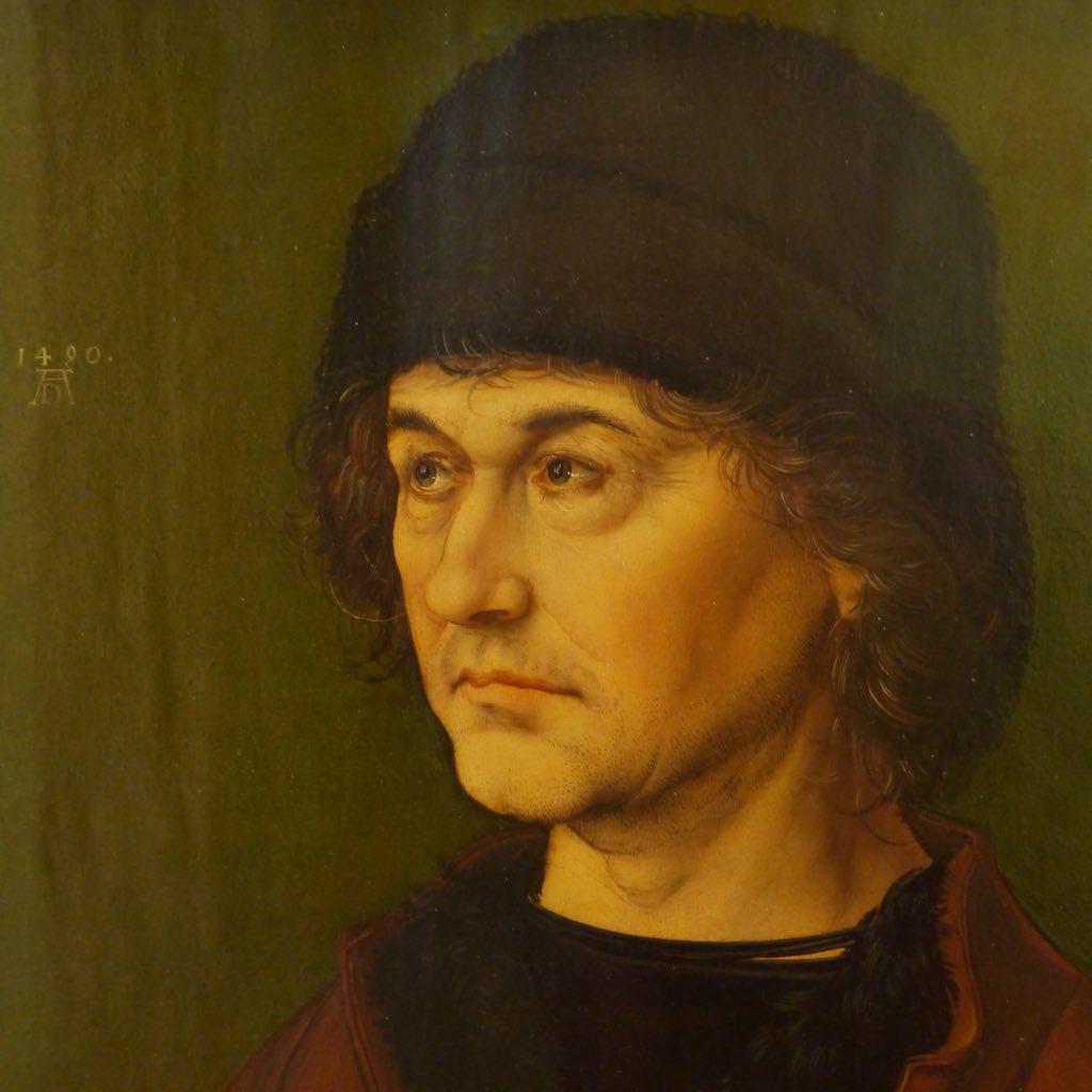 Das Brustporträt eines Mannes vor einem grünen Hintergrund. Frühes Meisterwerk von Albrecht Dürer in den Uffizien.