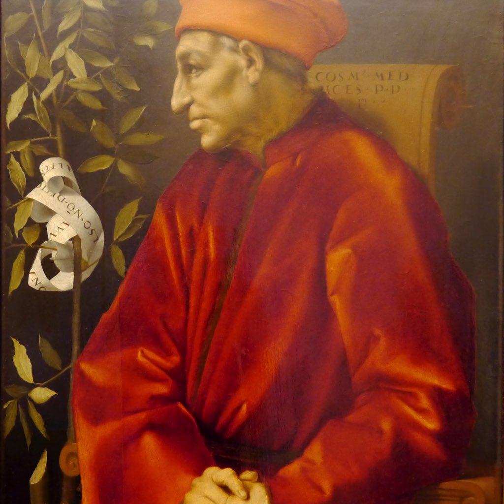 Ein Mann, gekleidet in einen roten Mantel, der auf einem Stuhl sitzt. Links vor ihm steht ein Lorbeerbaum um den eine Schriftrolle gewickelt ist. Der Mann trägt eine rote Mütze auf dem Kopf. Sein Gesicht ist im Profil dargestellt, dadurch ist in diesem Meisterwerk die starke, große Nase und das spitze Kinn von Cosimo dem Älteren besonders gut zu erkennen.