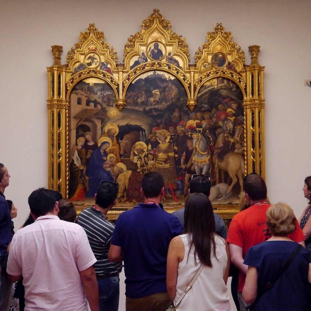 Ein Meisterwerk aus den Uffizien, vor dem sich viele Betrachter versammelt haben. Das Bild ist von einem goldenen Rahmen eingefasst. Dargestellt ist auf der linken Seite die Mutter Maria mit dem Christuskind. Davor Der Zug der Weisen aus dem Morgenland.