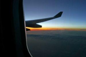 Tragfluegel vor Sonnenuntergang, aus dem Fenster eines fliegenden Flugzeugs fotografiert - Glosse zum Thema Flugreisen und Klimawandel