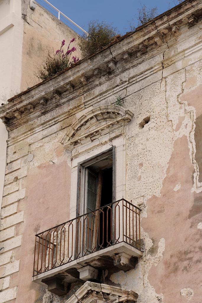 Eine Hausfassade aus dem 19. Jahrhundert in Trani. Ein Fenster mit einem Balkon. Das Fenster fehlt. Der rosa Putz fällt von der Wand. Auf der Dachtraufe wachsen Pflanzen.