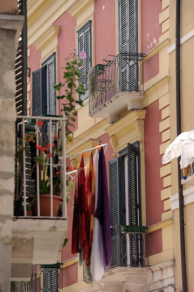 Schmiedeiserne Balkone in einer schmalen Gasse in Trani. Auf den Balkonen sind Wäscheleinen aufgespannt, auf denen Wäsche trocknet.