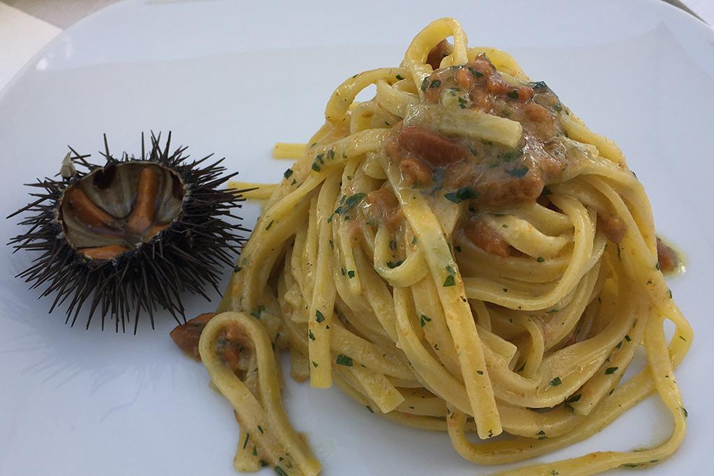 Ein weißer Teller mit Linguine auf denen das Fleisch der Ricci di Mare augehäuft ist. Rechts liegt ein aufgeschnittener Seeigel auf dem Teller.