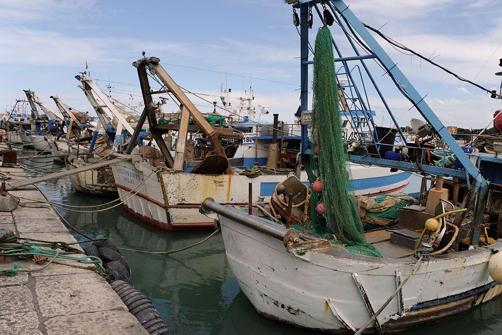 Eine Kaimauer im Hafen von Trani, an der mit Tauen Kutter festgemacht sind. An Bord der Schiffe liegen große Fischernetze.