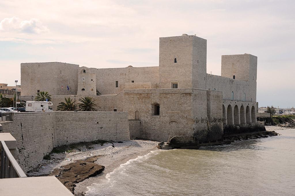 Ein kubisches Gebäude mit vier Türmen direkt am Meer. Das staufische Kastell von Trani ist auf weißen Steinquadern errichtet.