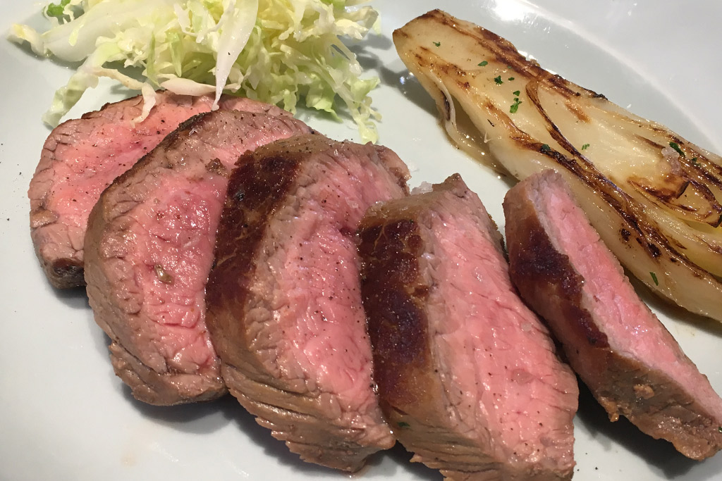 Ein Teller mit aufgeschnittenem Rindfleisch und Gemüse.