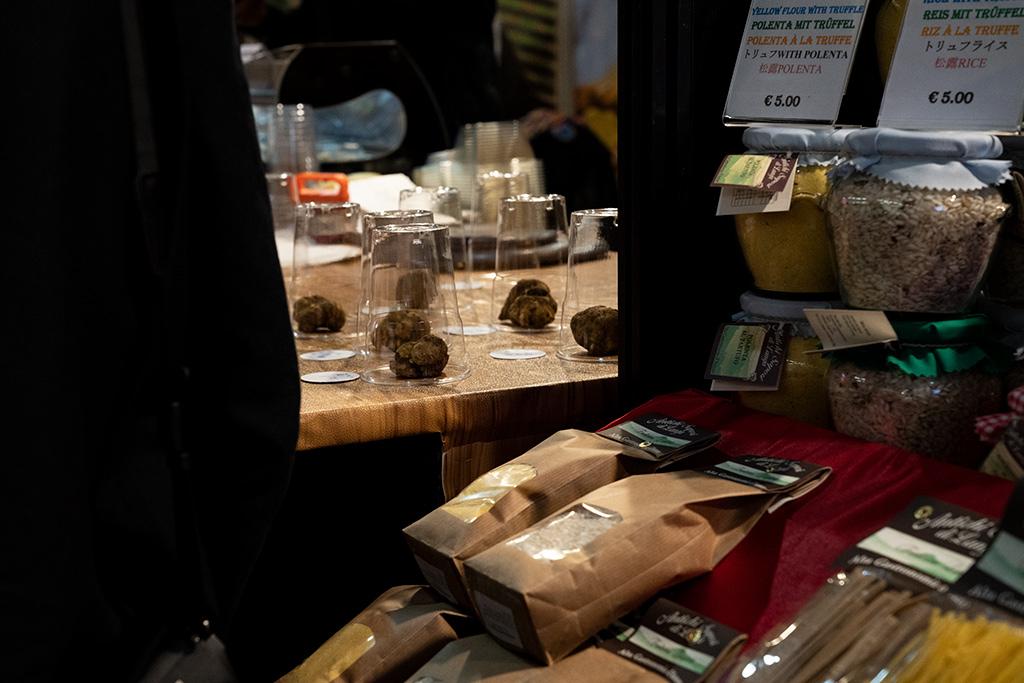 Verkaufstand auf dem Trüffelmarkt in Alba. Schwarze Trüffel werden unter einem Glas angeboten. Davor Nudeln mit Trüffeln.