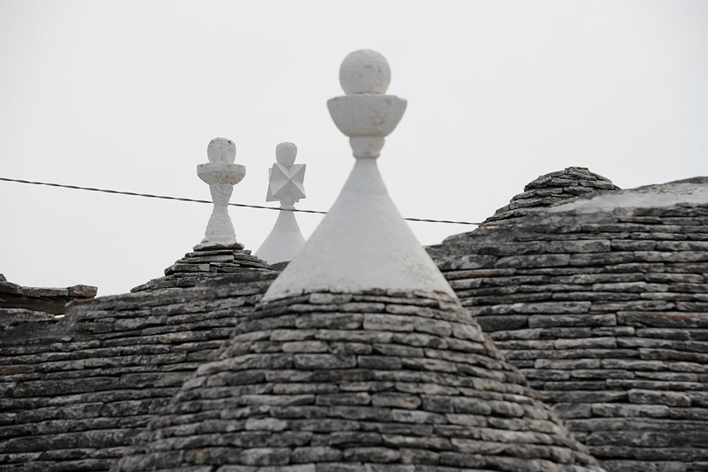 Drei kleine geometrische Formen bilden die Spitze von Kegeln der Dächer.
