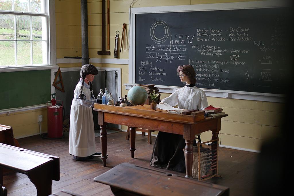 Vor der Tafel sitzt eine Lehrerin in einem altmodischen Kleid vor ihrem Pult. Am Tisch steht eine Schülerin weißem Kleid. Display mit Puppen aus dem Kauri Museum in Matakohe.