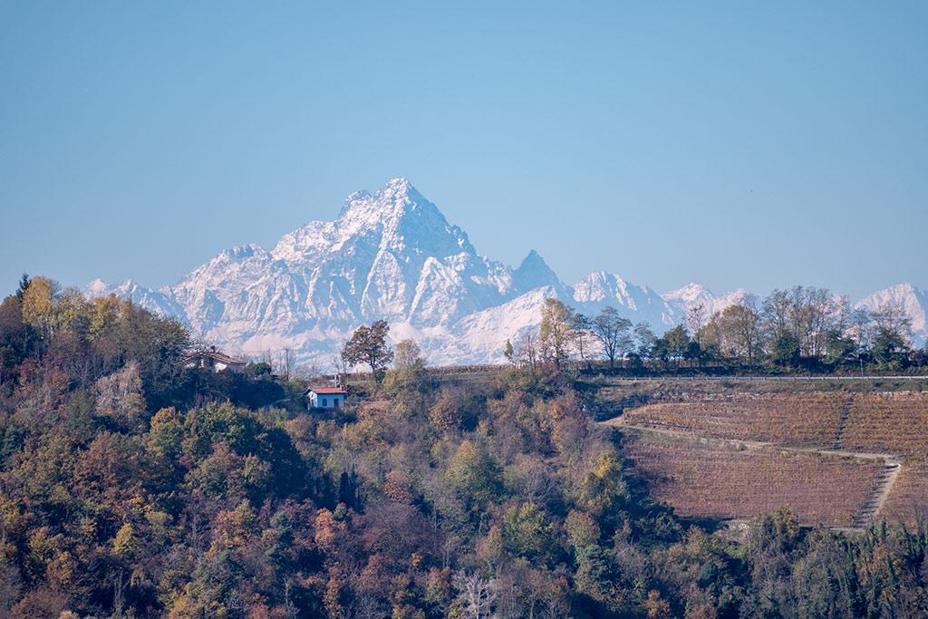 Der Gipfel des Monviso mit Schnee. Davor eine Landschaft im Piemont.