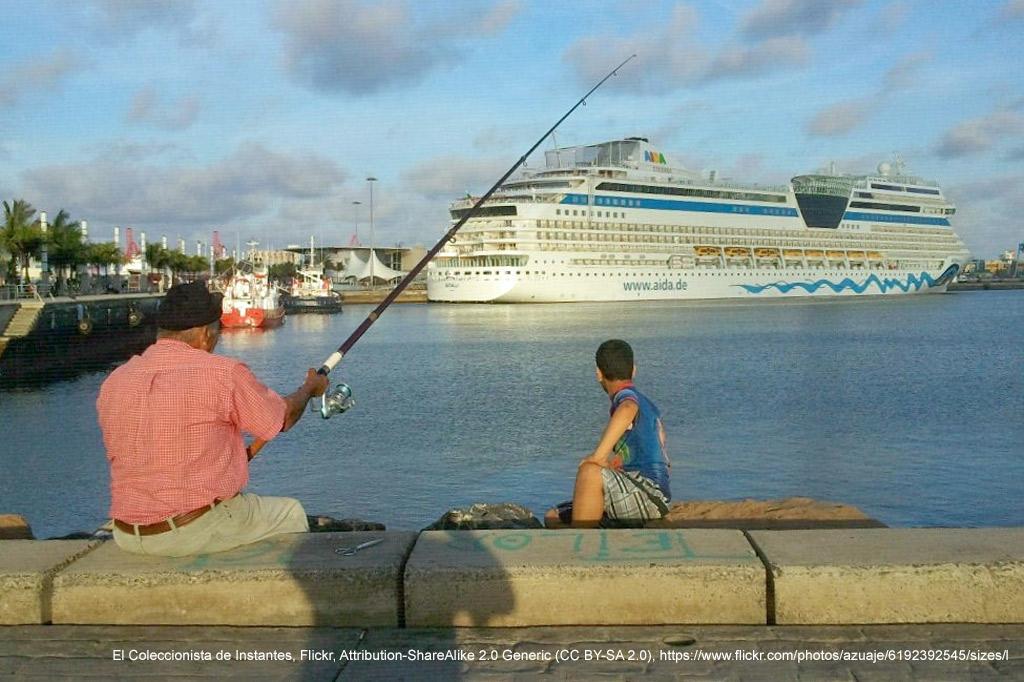 Die Kanaren: Armut durch Massentourismus – Ein älterer Mann und ein Junge angeln am Hafen. Im Hintergrund liegt ein Kreuzfahrtschiff