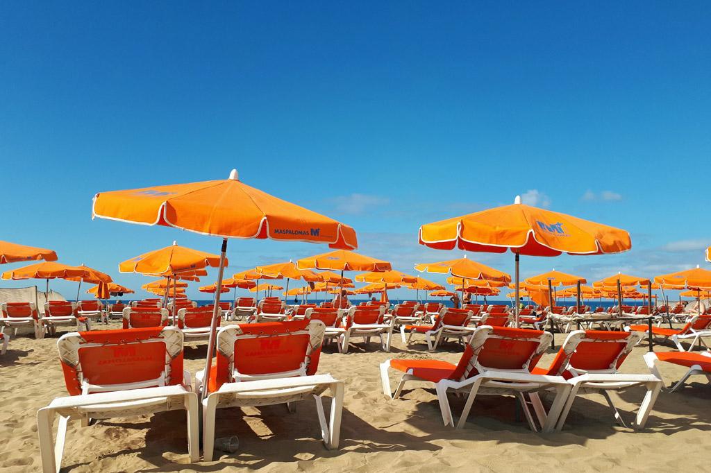 Die Kanaren: Armut durch Massentourismus – Eine unübersehbare Anzahl leerer oranger Strandliegen unter orangen Sonnenschirmen am Strand von Maspalomas, Gran Canaria