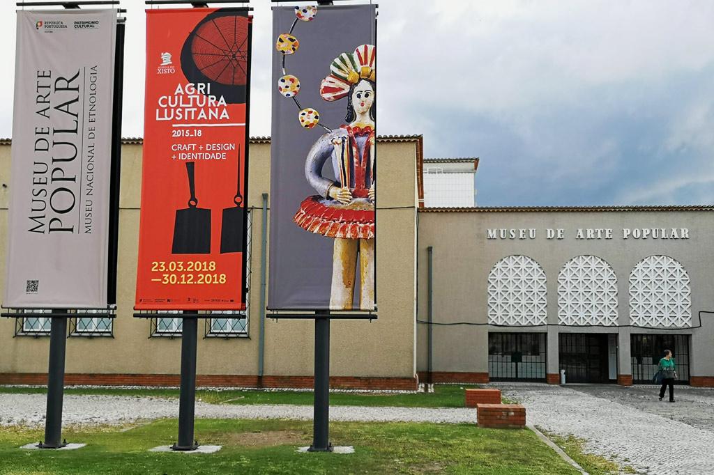 Ab aufs Land: Dorfkultur made in Portugal – Fassade des Lissaboner Heimatmuseums Museu de Arte Popular. Im Vordergrund Hinweisschilder auf die aktuelle Ausstellung über die sog. Schieferdörfer im Landesinneren, die noch bis zum 23.12. diesen Jahres zu sehen ist.