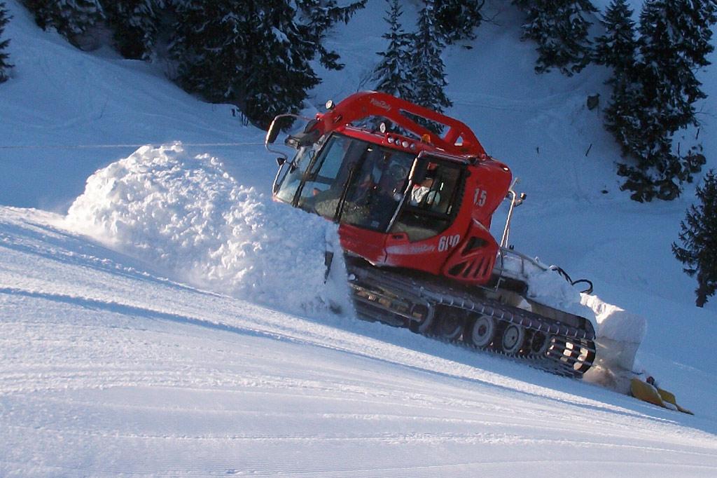 Ein Pistenfahrzeug präpariert einen Skiabfahrtshang – Wintersport in den Alpen: Schnee 4.0 vs. Klimawandel