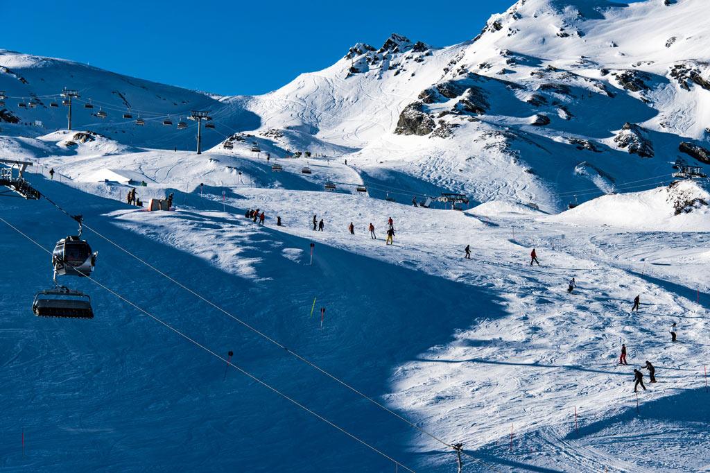 Skipiste mit Lift in den Alpen – Wintersport in den Alpen: Schnee 4.0 vs. Klimawandel