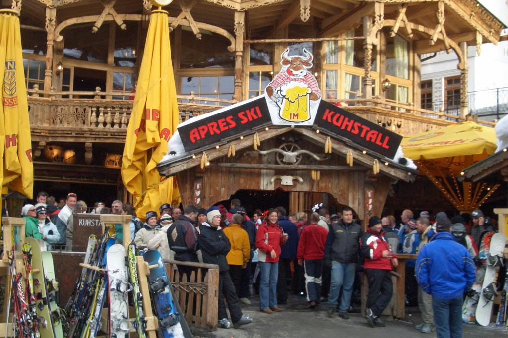 "Skifahrer stehen vor dem Partylokal ""Après-Ski Kuhstall"" – Wintersport in den Alpen: Schnee 4.0 vs. Klimawandel"