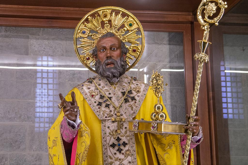 Der heilige Nikolaus als Skulptur mit dunkler Haut, Heiligenschein und einem Bischofsstab.